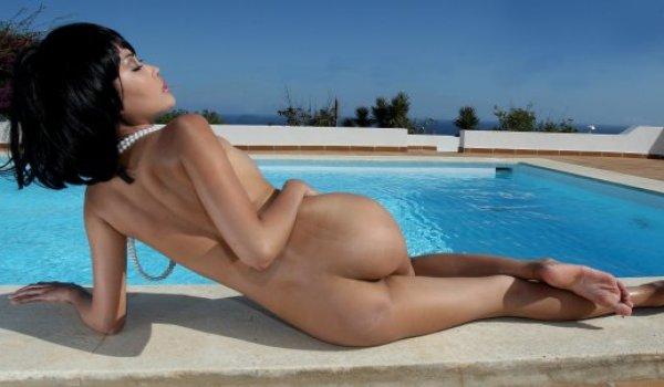 Asiática magrinha de cabelos curtos na beirada da piscina