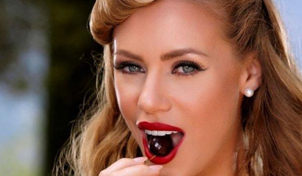 Loira quente comendo uma cereja e se masturba com um consolo