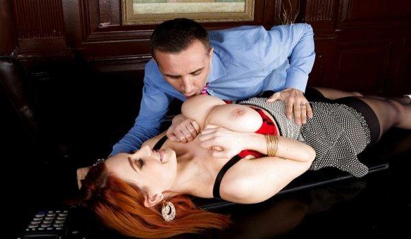 Secretaria deitada na mesa e seu patrão chupando os seus seios