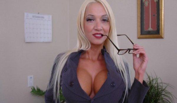 Secretaria tesuda mordendo o óculos e mostrando os seus peitões