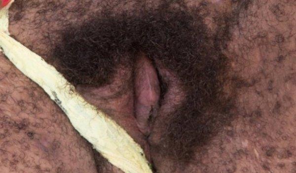 Negra puxando a calcinha para mostrar a xana cabeluda
